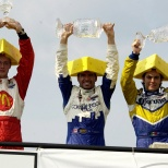 2004: Alex Tagliani (cen.) esperó 85 participaciones para subir a lo más alto del podium, en una edición del GP de Road America en la que inició 13° y, gracias a una bandera amarilla, le bastó con superar a Rodolfo Lavín (der.) a cuatro vueltas del final. Es su única victoria en la especialidad (FOTO: Archivo)